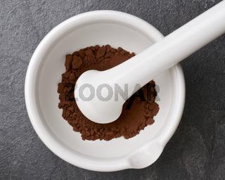 Kakaopulver in einem Mörser mit Pistill