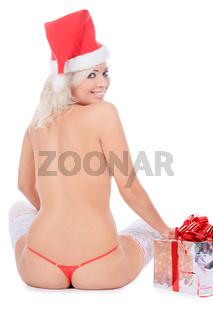 Wonderful female in santa hat and white stockings near Christmas gift