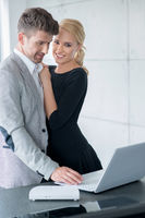 Lovers in Trendy Attire Testing Displayed Laptop