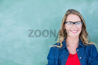 Smiling geeky teacher standing in front of blackboard