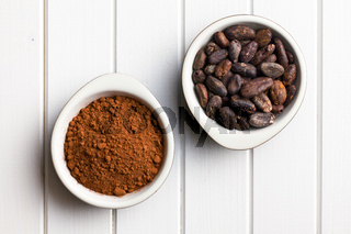 cocoa beans and cocoa powder in bowls