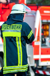 Rücken eines Feuerwehrmannes mit Helm vor seinem Einsatzfahrzeug