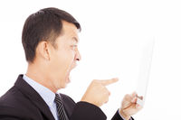 businessman holding a tablet or ipad and screaming to point it