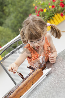 Little girl decorating the chocolate cake