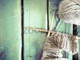 Colorful ball of yarn and knitting on a wooden table