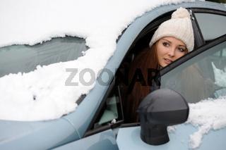 Junge Frau in einem eingeschneiten Auto