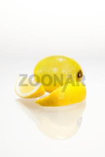 Angeschnittene Zitrone mit Spiegelung vor weißem Hintergrund