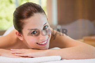 Beautiful woman lying on massage table at spa center