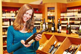Frau kauft Flasche Wein im Getränkemarkt