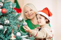 Enkel hilft Großmutter beim Schmücken vom Weihnachtsbaum