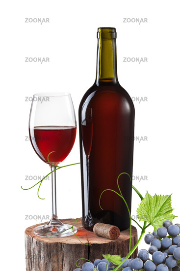 Glass of red wine, bottle and grape on stump isolated on white