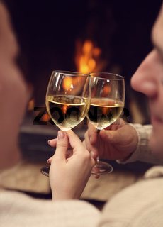 Romantic young couple toasting wineglasses in front of lit fireplace