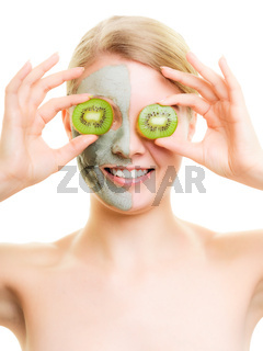 Skin care. Woman in clay mask with kiwi on face