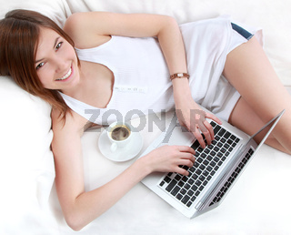Pretty woman lying on sofa with laptop and cap of coffe