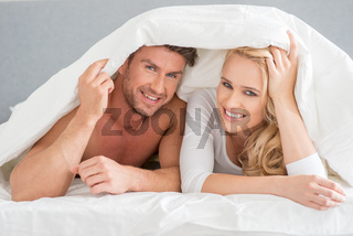 Young couple covering themselves in the duvet