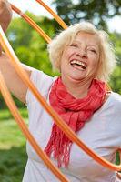 Lachende Seniorin treibt Sport mit Reifen