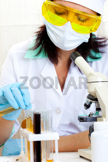 doctor looking at a test tube of yellow solution