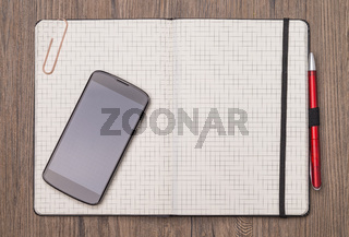 Notizbuch und Telefon auf Holztisch