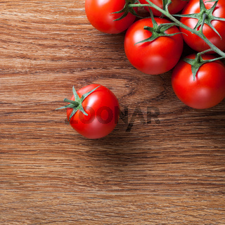 red tomatoes with green salad on wood