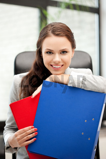 young businesswoman with folders sitting in chair