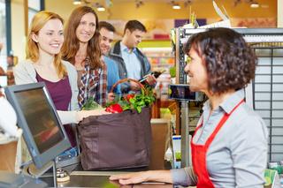 Frau in Warteschlange an Kasse im Supermarkt