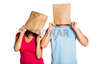 Young couple with bags over heads
