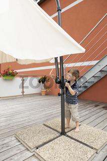 Little boy opens the parasol