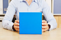 Mann hält blaues Geschenk in der Hand