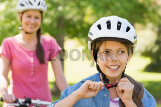 Smiling woman with her daughter riding a bicycle