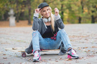 Woman with a cute smile sitting on skate board