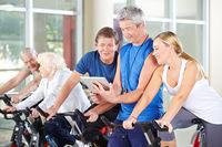 Trainer mit Tablet PC trainiert Gruppe im Fitnesscenter