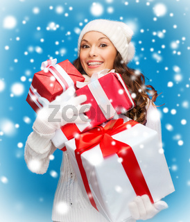 woman in sweater and hat with many gift boxes