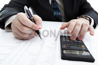 businessman holding a pen and counts the budget