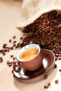 A cup of coffee and roasted coffee beans
