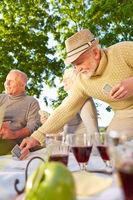 Senioren spielen Karten im Garten
