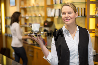 waitress presenting cup of coffee or tea
