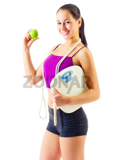 Sporty girl with apple and scales isolated
