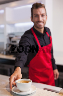 Happy young barista putting cup of coffee down on counter