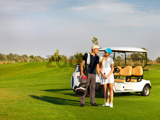 Young sportive couple playing golf on a golf course