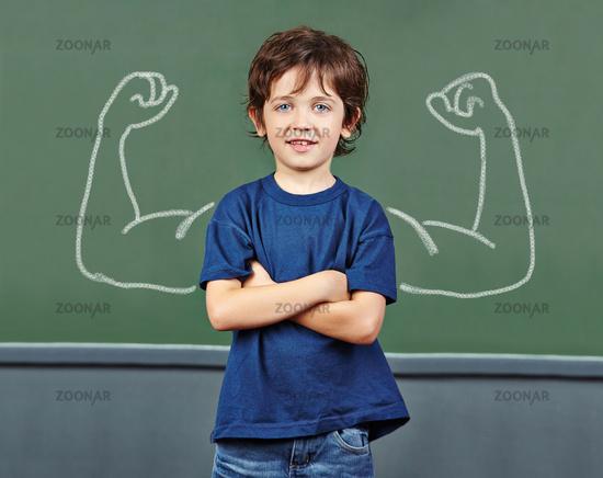 Kind mit Muskeln auf Tafel in Schule