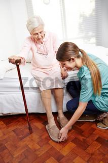 Altenpfleger hilft Seniorin beim Aufstehen