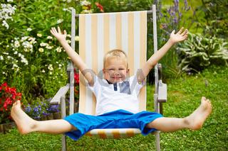 Kind liegt entspannt auf Liegestuhl im Garten