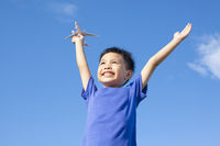 joyful little boy holding a toy with blue sky background