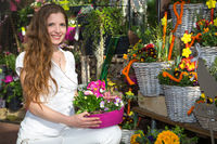 Woman in flower shop among flower arrangements