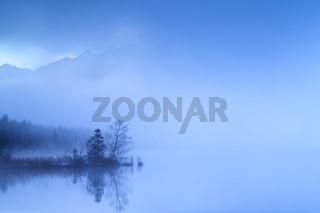 dense fog in dusk over alpine lake