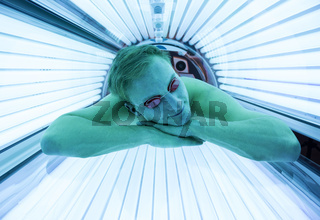 Man with sunglasses on tanning bed in solarium