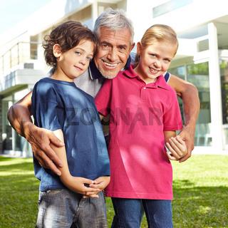 Lachender Opa mit Enkeln im Garten