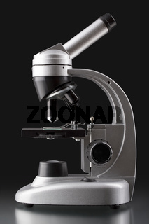 close up of a silver microscope, with black background