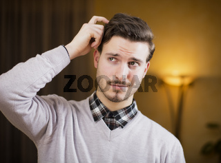 Confused or doubtful young man scratching his head and looking up. Indoors shot in a living room