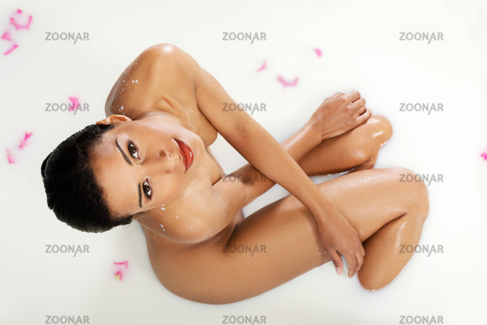 Attractive naked woman lying in a milk-bath. Up front view.